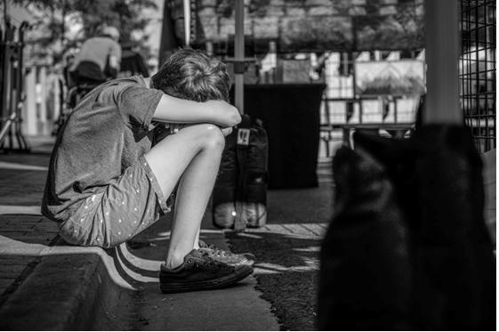 a boy sitting with head down