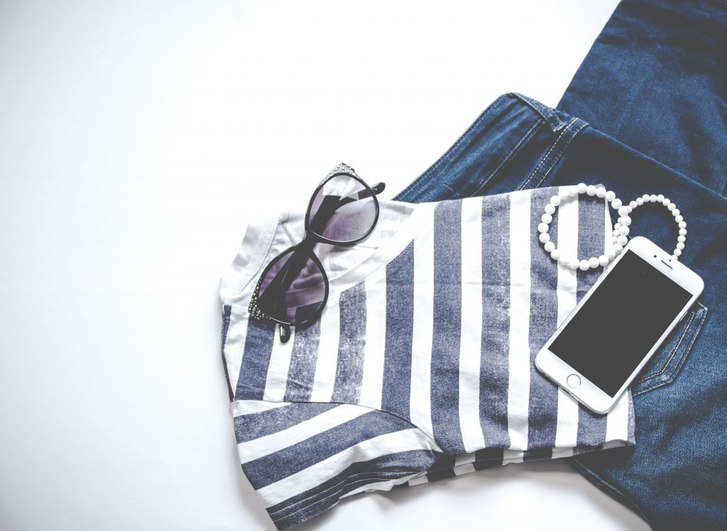 A sun glass, phone, jewlery, jeans and vest.