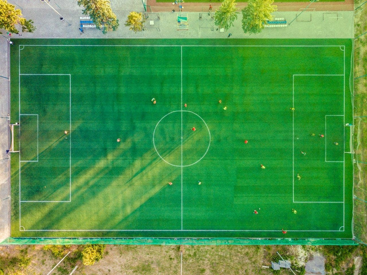 Green football pitch with footballers